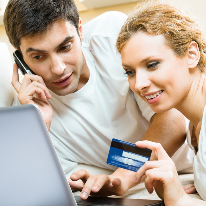 Cheerful couple paying by plastic card